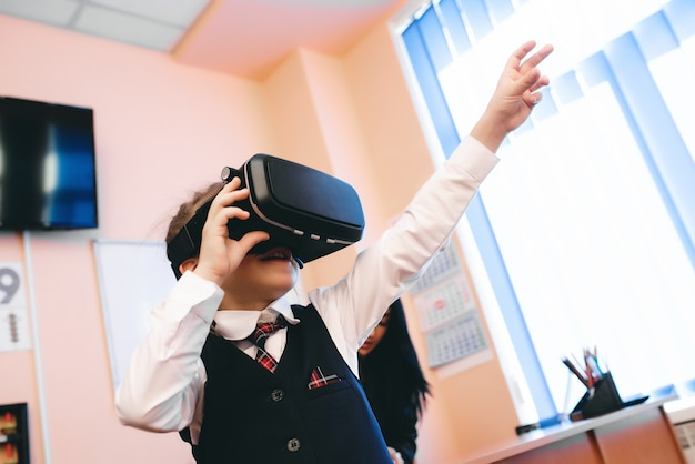 Children with virtual reality glasses are in the school office