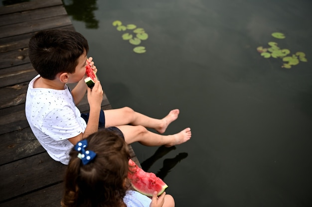 桟橋で休んでいるスイカと川の水の下で成長している睡蓮を賞賛している子供たち。男の子と女の子が屋外で楽しんでいます。田舎の夏休みのコンセプト。
