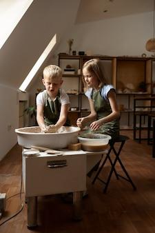 Дети работают на гончарном круге в мастерской. урок лепки из глины в художественной школе. юные мастера народных промыслов, приятное увлечение, счастливое детство.