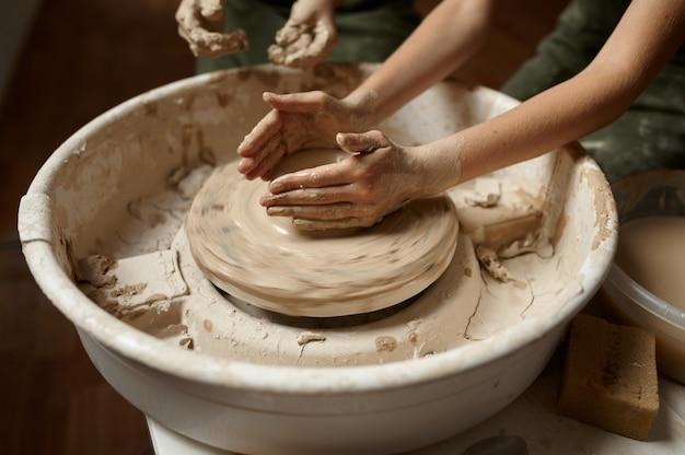 Дети работают на гончарном круге в мастерской, вид сверху на руки. урок лепки из глины в художественной школе. юные мастера народных промыслов, приятное увлечение, счастливое детство