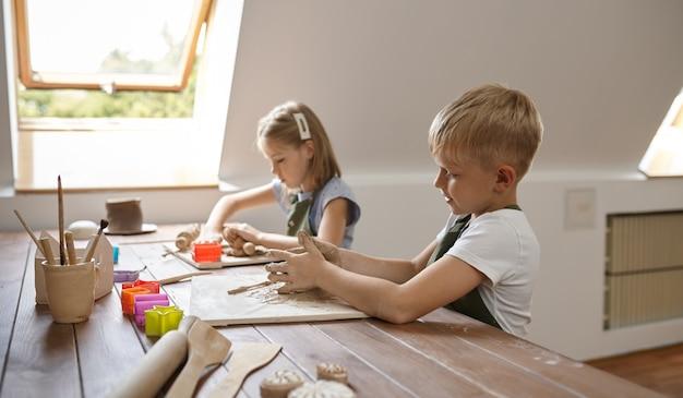 Дети работают с глиной, уроки лепки в мастерской. урок в художественной школе. юные мастера народных промыслов, приятное увлечение, счастливое детство