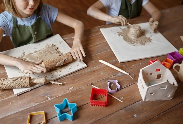 Дети работают с глиной, уроки лепки в мастерской. урок в художественной школе. юные мастера народных промыслов, приятное увлечение, счастливое детство.