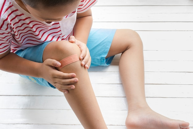 Children wound or the boy had an accident sitting on wooden white background.
