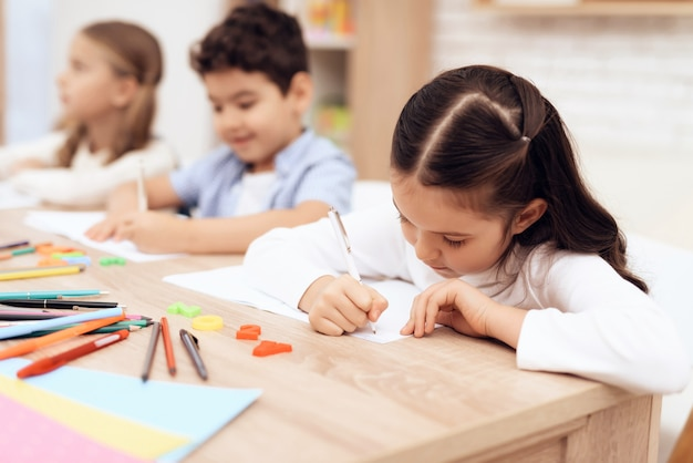 Children write in notebooks with a pen.
