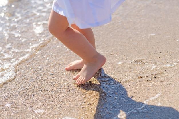 Детские босые ноги на песке морского пляжа