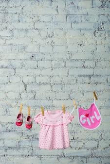 흰색 벽돌 벽에 밧줄에 마른 소녀를위한 어린이 턱받이 드레스와 빨간 신발