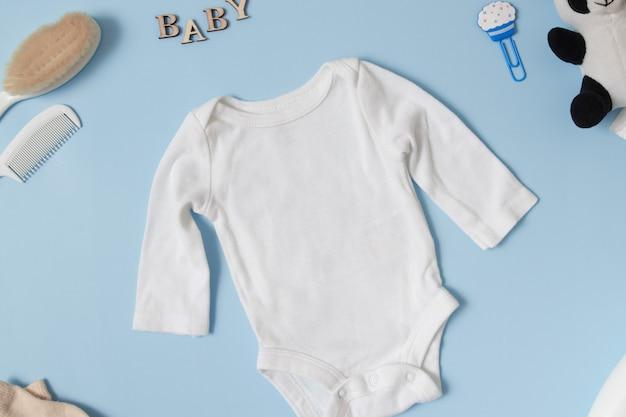 Детская одежда, вид сверху, макет белого детского боди на синем фоне, место вашего текста или логотипа