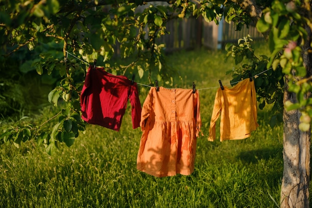 Детская цветная одежда висит на бельевой веревке и сушится после стирки в саду.