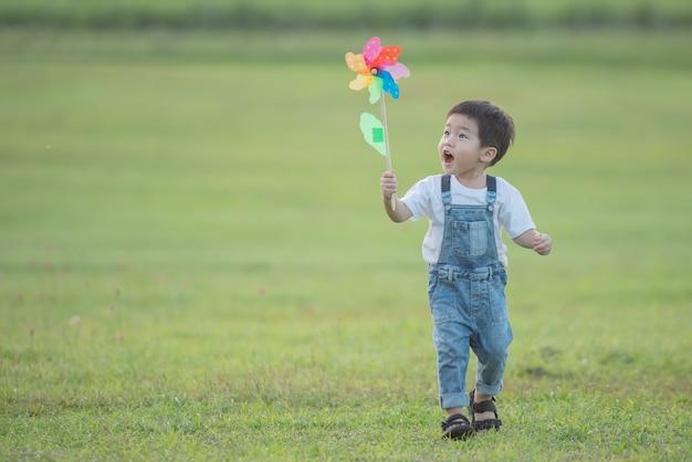 Giocattolo colorato mulino a vento per bambini. bambino che ride che gioca felicemente. il ragazzino soffia contro un mulino a vento colorato in estate al campo estivo sotto il sole.