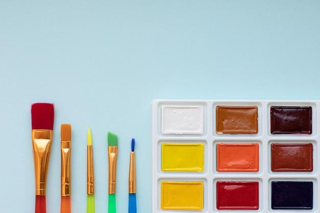 Детское творчество, хобби, концепция рисования палитра акварельных красок и пять разноцветных кистей на синей поверхности вид сверху