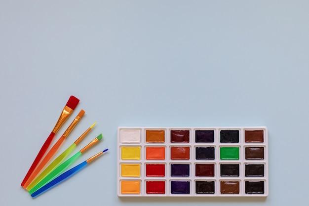 Детское творчество, хобби, концепция рисования палитра акварельных красок и пять разноцветных кистей