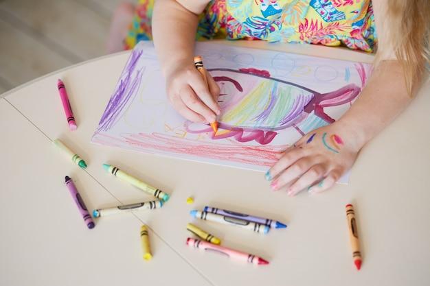 Детское творчество. маленькая детская девочка рисует восковыми карандашами дома. концепция дистанционного обучения онлайн на период глобального карантина.