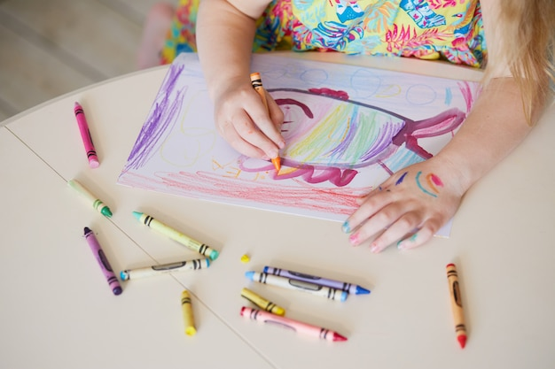 Childrens creativity. little child girl draws with wax pencils at home. the concept of distance learning online for the period of global quarantine.
