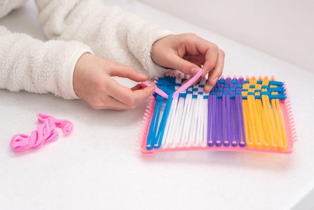 着色された糸ロープで織る子供の創造性