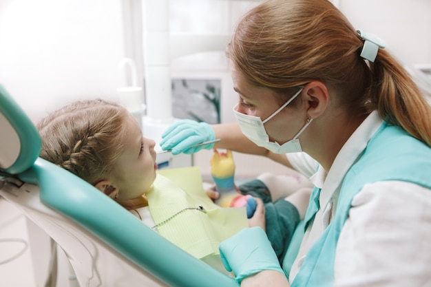 Childrens dentist working at her clinic, examining teeth of little girl