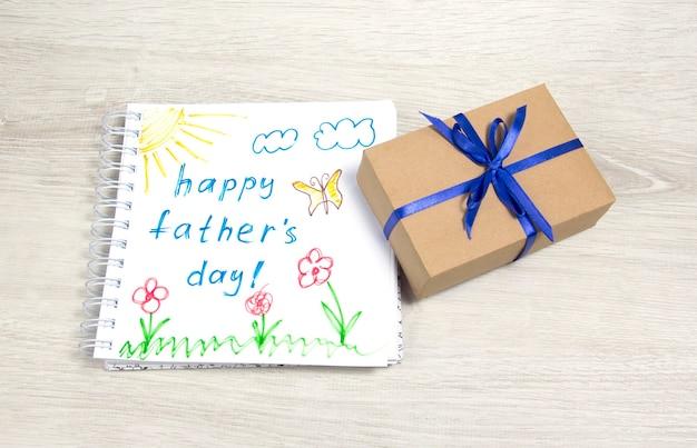 연필을 사용하여 행복한 아버지의 날을 그리는 어린이 파란색 리본이 달린 선물 상자