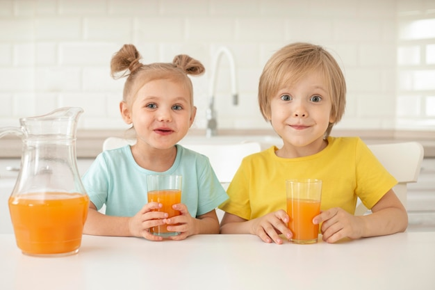 Childrens drinking juice at home
