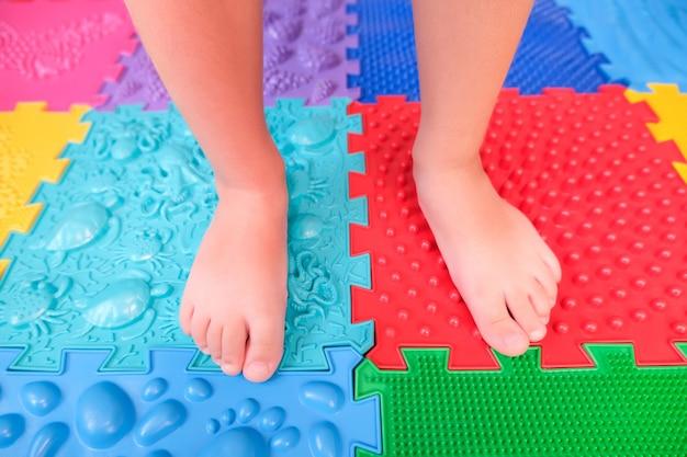 整形外科用マットの上の子供の足、扁平足の予防。