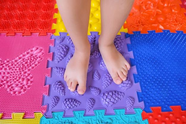 Детские ножки на ортопедических ковриках, профилактика плоскостопия.