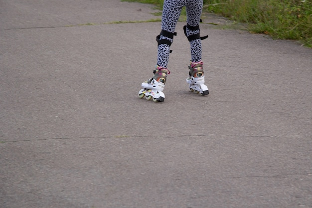 Childrens feet with protection on their knees in white blue rollersa child rides  on rollers