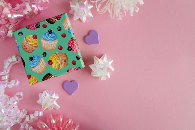Childrens gift with colorful confetti on the pink background