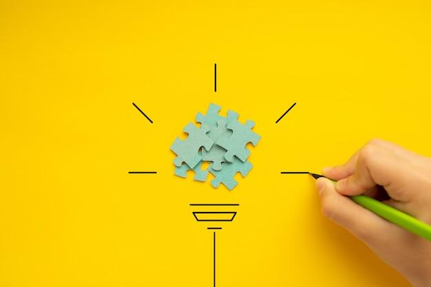 子供の手が黒いマーカーで電球を描く黄色の背景に電球が見える