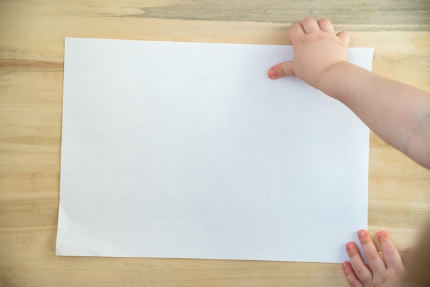 Childrens hand holding blank white paper sheet on wooden background.