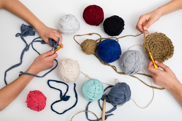 Childrens hands are crocheted and thread. view from above