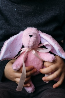 子供の手は小さな柔らかいウサギのおもちゃを持っています。