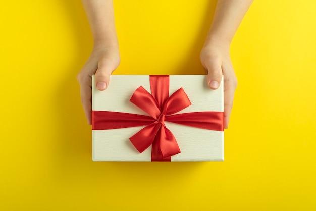 어린이 손에 노란색 선물을 들고있다