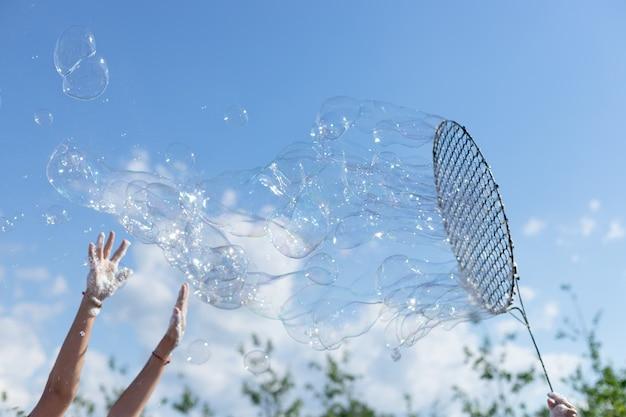 Детские руки ловят большие мыльные пузыри на фоне голубого неба счастливое детство