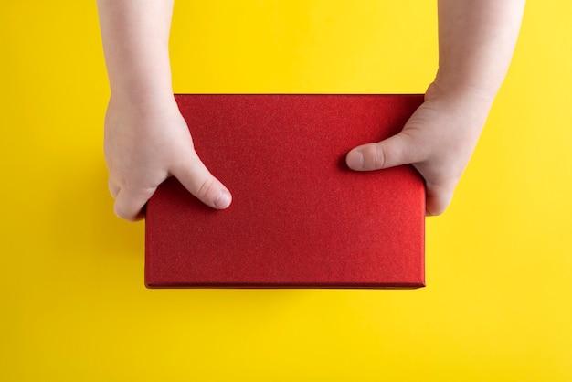 子供の手は黄色の背景に赤い段ボール箱を保持します。上面図。スペースをコピーします。モックアップ