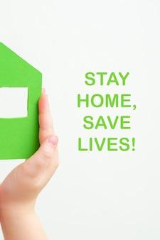 Детские руки держат половину бумажного зеленого дома со словами: оставайся дома, спасай жизни на белом