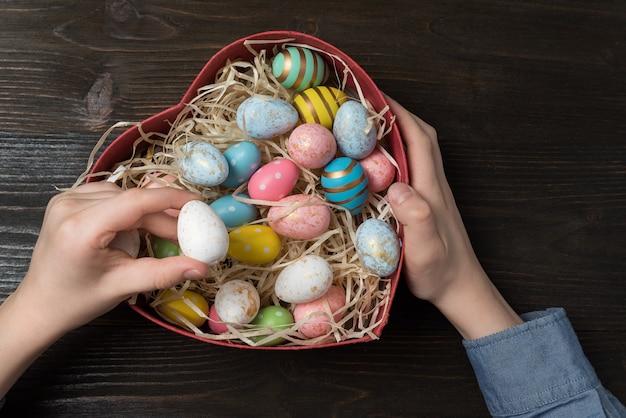 Детские руки, держащие коробку сердечной формы красочными пасхальными яйцами. концепция пасхального подарка