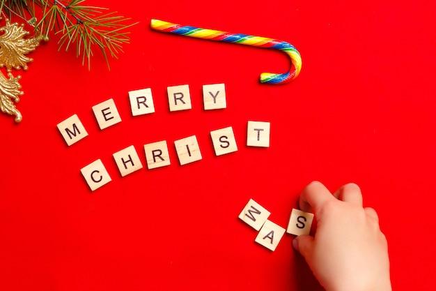 Детские руки составляют слово с рождеством. украшение карамельной тростью.