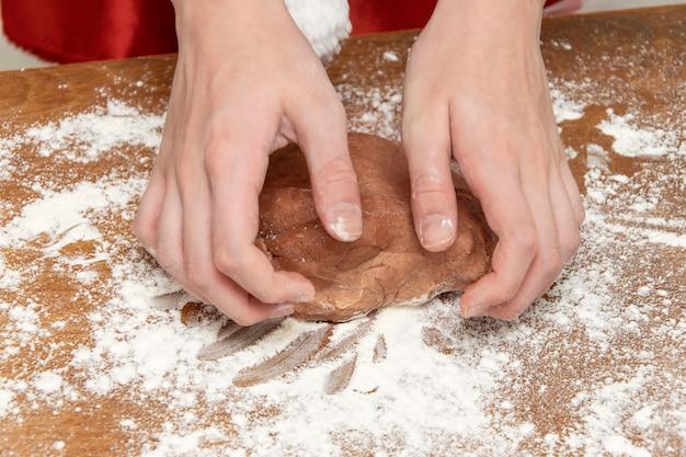 Детские руки раскатывают тесто для имбирных пряников. руки крупным планом.