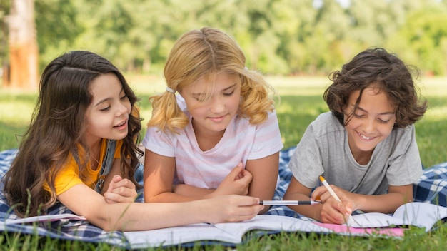 Childrens in park writing