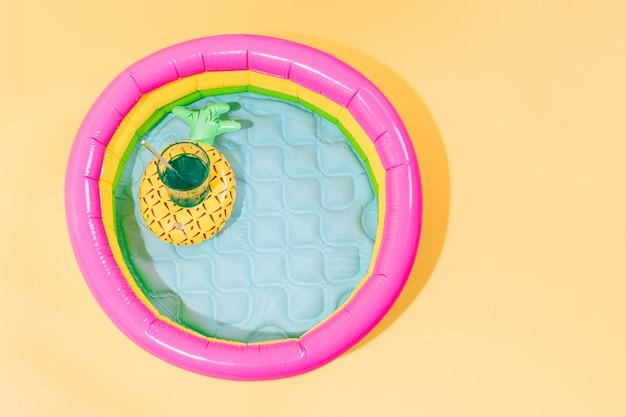 Детский бассейн с надувной лодкой в форме ананаса с коктейльным видом сверху