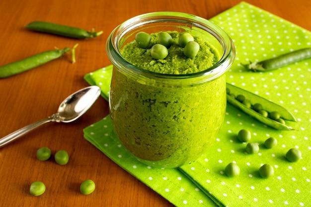 緑のナプキンのガラスの瓶にエンドウ豆と子供たちのピューレ