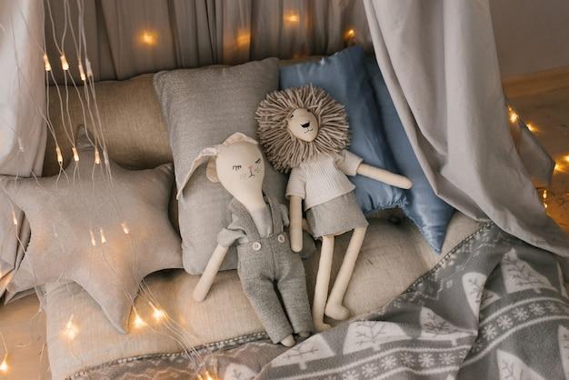 Детская комната в пастельных оттенках серого и синего с тканевой палаткой, игрушками и подушками.