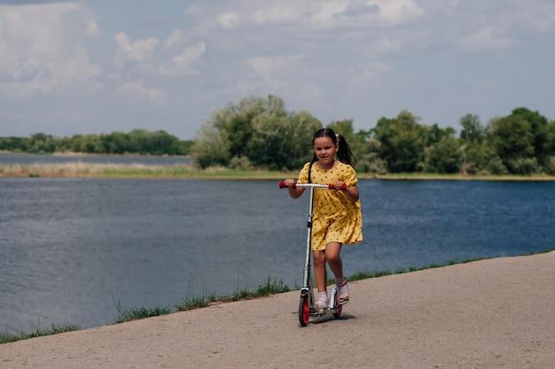 Детский спорт и семейные выходные ребенок катается на самокате по дорожке у пруда в ...