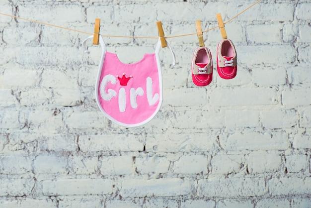 흰색 벽돌 벽에 밧줄에 어린이 유아 핑크 타액과 빨간 신발