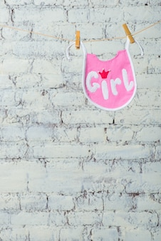 Childrens toddler pink saliva on a rope on a white brick wall background