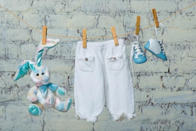 어린이 흰색 몸통 부츠 팬티와 흰색 벽돌 벽에 밧줄에 마른 장난감 토끼