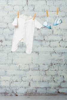 흰색 벽돌 벽에 밧줄에 어린이 흰색 몸과 파란색 신발