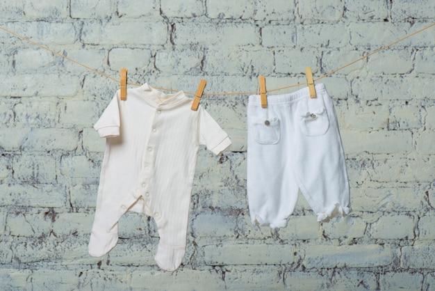 흰색 벽돌 벽에 밧줄에 마른 아이들의 하얀 몸과 팬티 스타킹