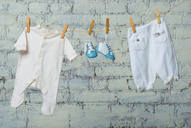 흰색 벽돌 벽에 로프에 건조 어린이 흰색 바디 부츠와 팬티 스타킹