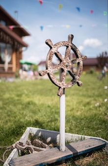 Childrens wooden steering wheel from a ship on the green grass
