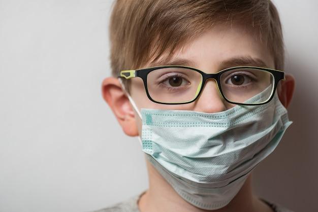 眼鏡と使い捨て防護マスクで子供の顔。インフルエンザに対するマスク保護を身に着けている男の子