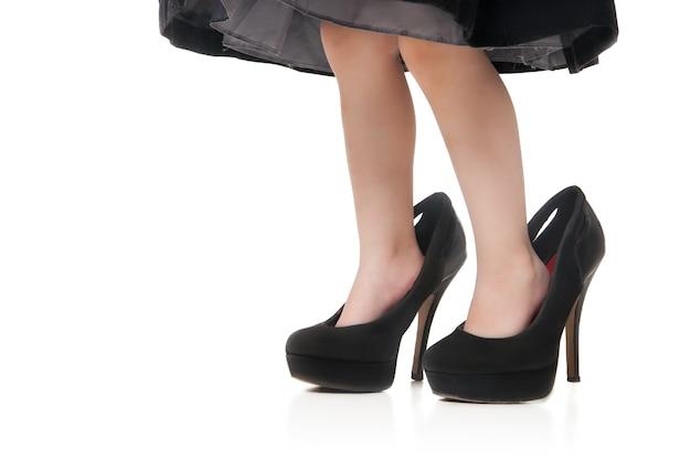 Ноги ребенка в больших зеленых туфлях на каблуках на белом фоне